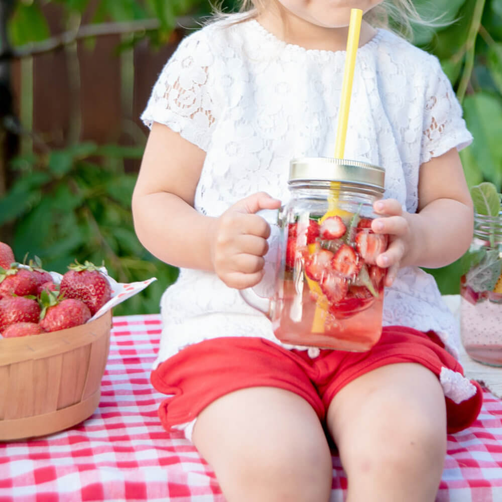Toddler girl drinking strawberry infused water from glass with straw