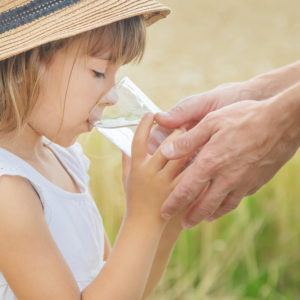 girl wearing hat and drinking water from glass