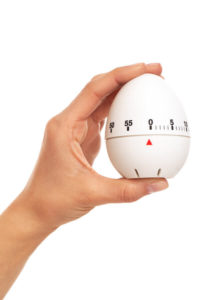 lady's hand holding egg timer