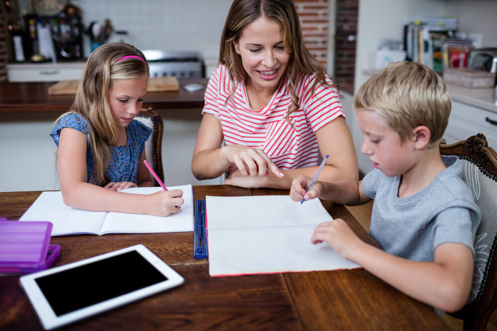Smiling mom with son and daughter creating a meal plan at the kitchen table