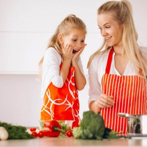 girl excited for dinner watching mom cooking